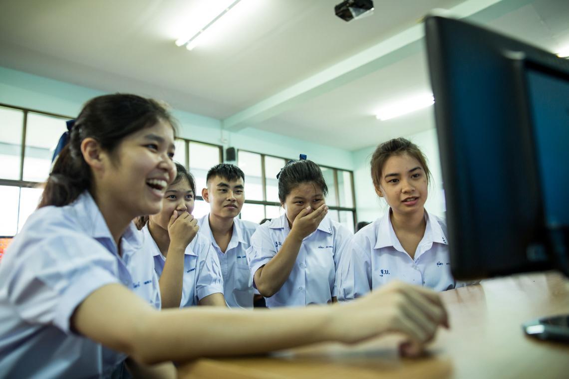 กลุ่มนักเรียนชายและหญิงกำลังนั่งอยู่หน้าจอคอมพิวเตอร์ พวกเขาใช้อินเทอร์เน็ตเพื่อหาข้อมูลที่พวกเขาสนใจ