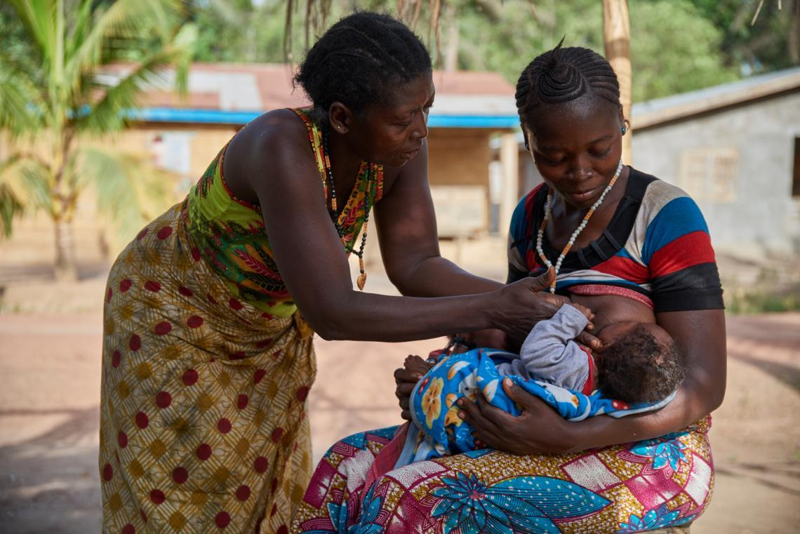 Zainab Kamara, supported by her mother, breastfeeds one of her twin sons, 3-month-old Alhassan Cargo, in Karineh Village in Sierra Leone.