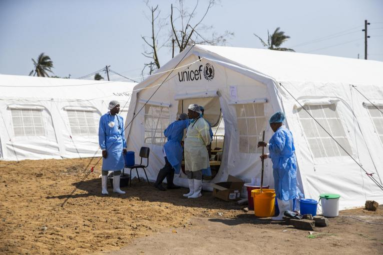 Health workers are standing outside a tent. UNICEF logo is at the top of the tent.