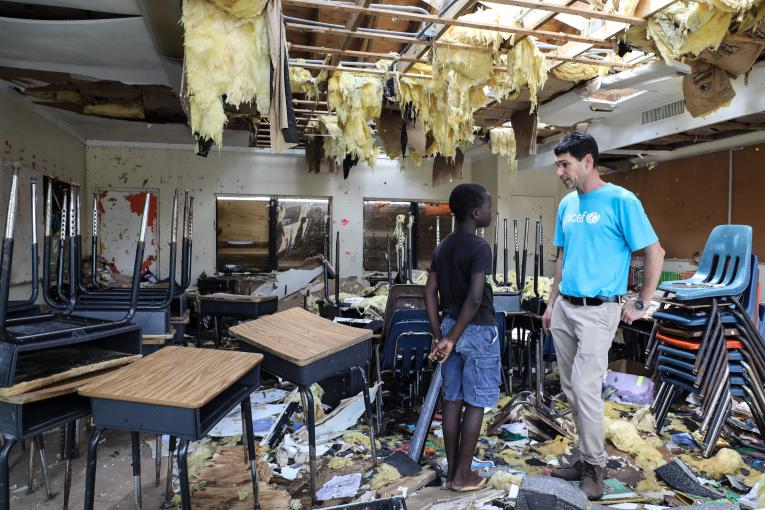 Torres Sanvilla, 10, talks to UNICEF's Regional Emergency Specialist Hanoch Barlevi in his totally destroyed classroom in Central Abaco public school.