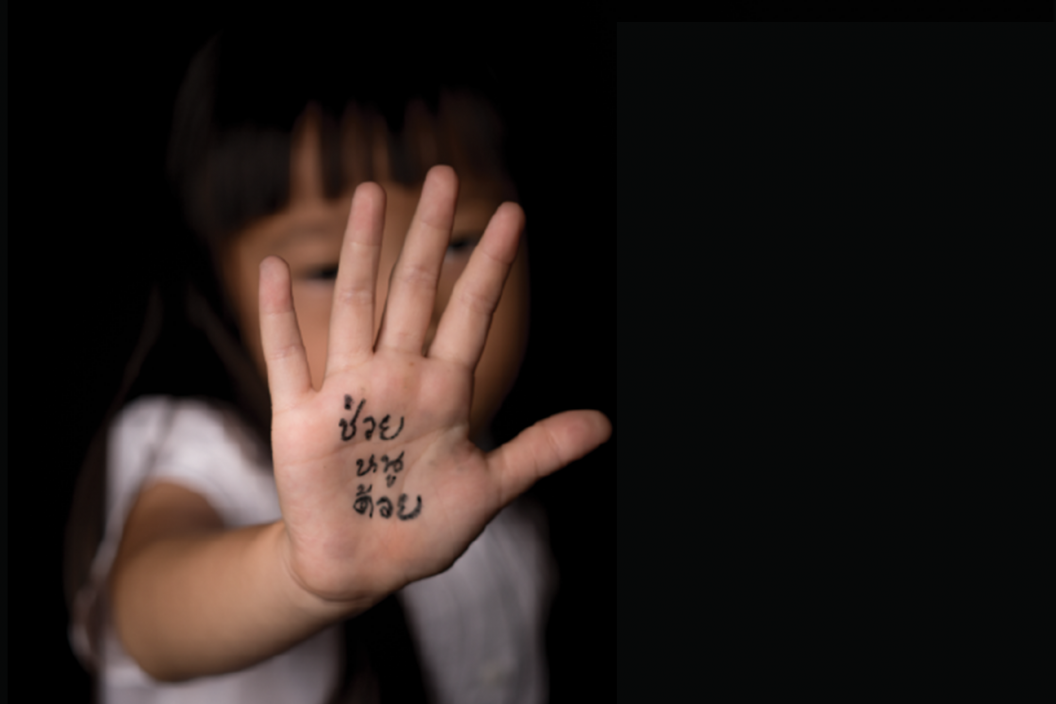 "A young girl stretching out her right hand. ""Help me"" is written on her hand."