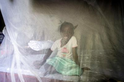 A girl sits behind a mosquito net