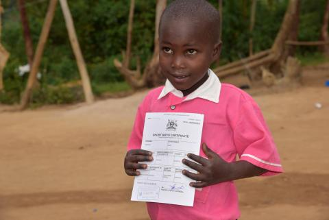 A girl holds her birth certificate