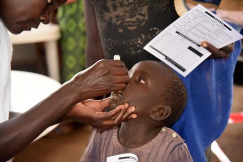A child receives a dose of oral vaccine