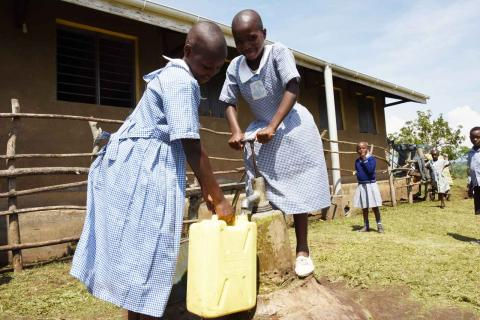 A girl holds a jerry can under a spout with another girl pumps water into it