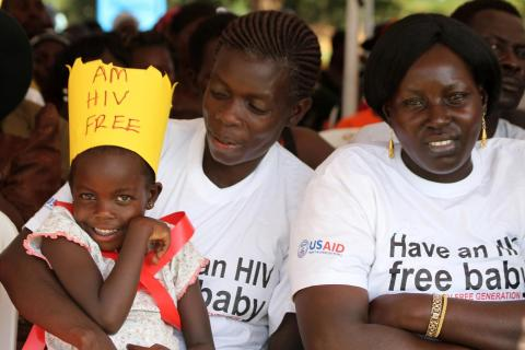 Two women and a girl, the girl is wearing a yellow paper crown reading 'am HIV free'