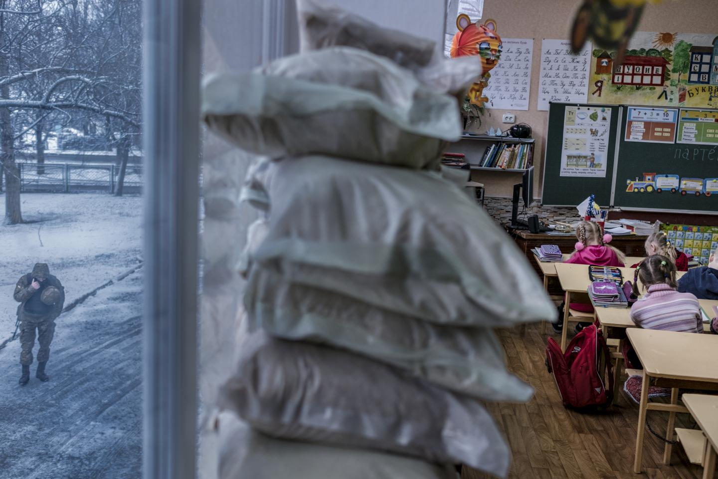 An armed police officer (left) patrols outside a classroom of first graders where the windows have been covered with sandbags, at a school in Marinka, Donetsk Oblast, Ukraine, Wednesday 22 November 2017.