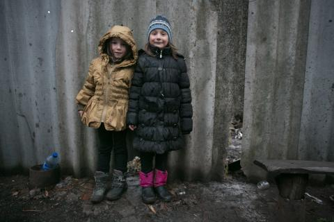 Sisters Sofia (6 years old) on the left and Karyna (7 years old) on the right stand near a fence of their house in Olenivka settlement in the non-government controlled part of Donetsk region.