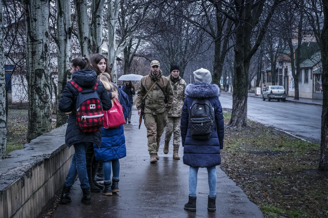 Soldiers and students walk on a street in Krasnohorivka, Donetsk Oblast, Ukraine, Tuesday 21 November 2017.