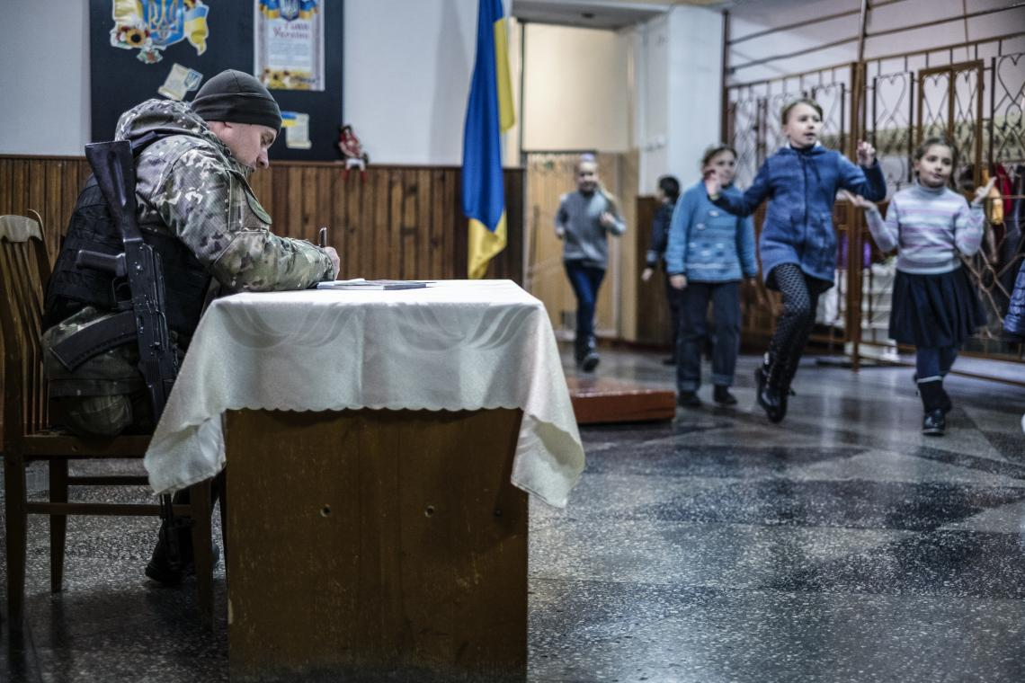 An armed guard sits in the lobby of a school in Marinka, Donetsk Oblast, Ukraine, Wednesday 22 November 2