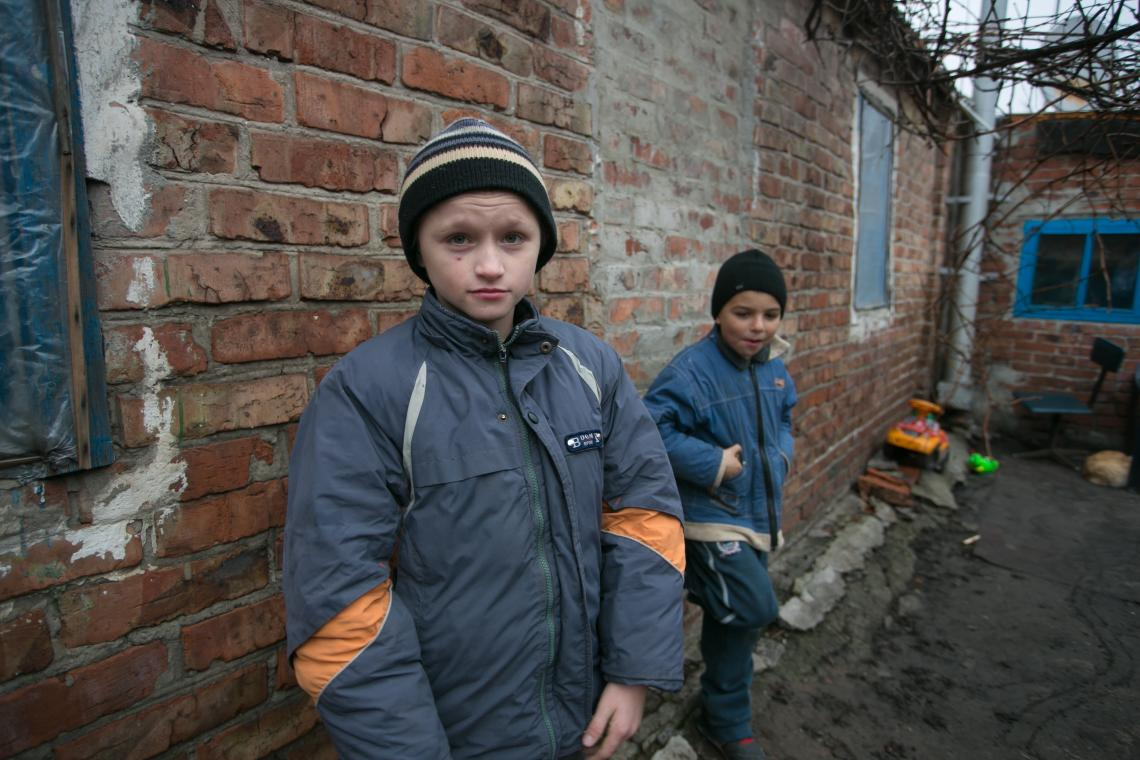 Vitia, 11, stands with his friend Vania, 9, in the yard of Vitia's house in Avdiivka, Donetsk region. One window is laid out with bricks and the other ones are covered in polyethylene film in an attempt to protect the house from wind and cold.