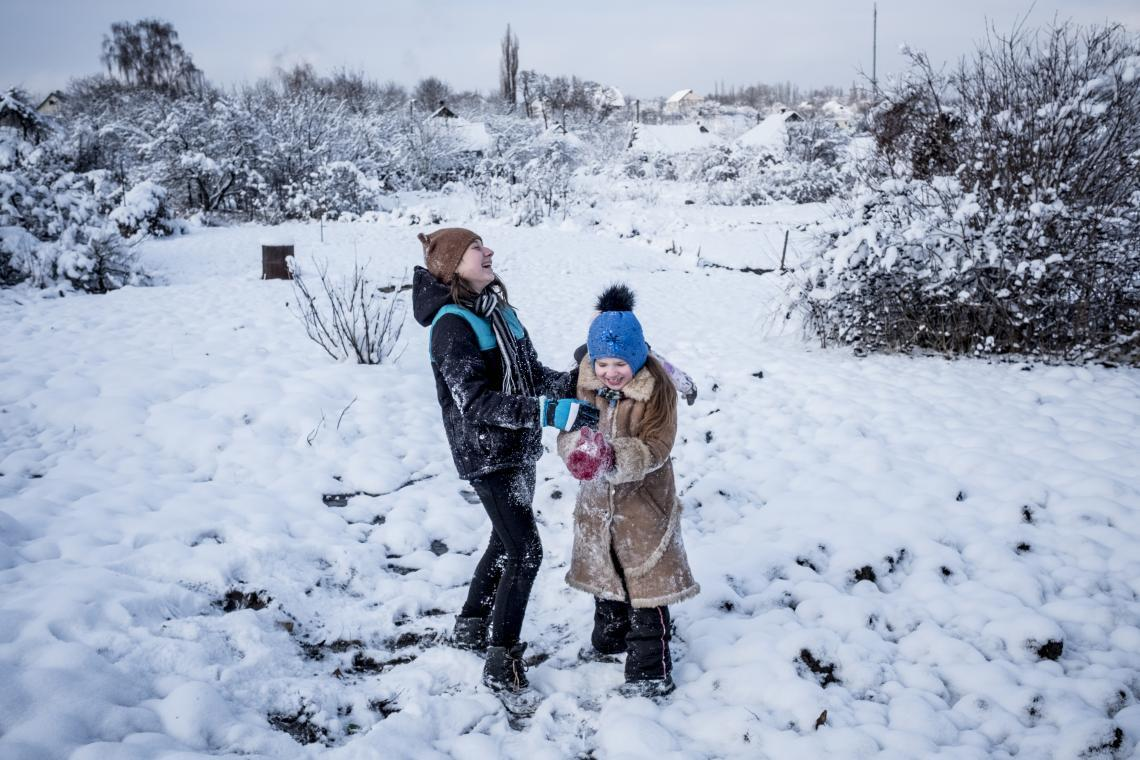 Two sisters play in the snow outside their home in eastern Ukraine. Even this is dangerous with shelling a constant threat.