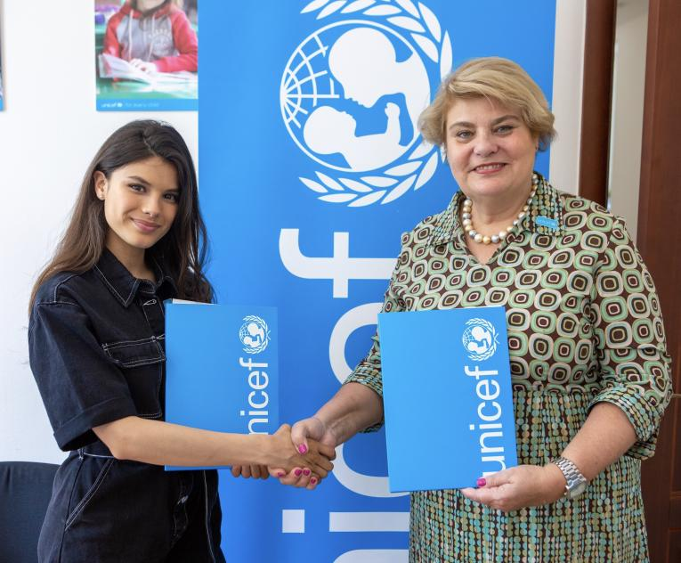 A singer and UNICEF Representaive shaking hands