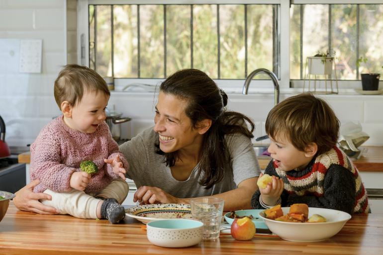 Madre con sus dos hijos junto a mesada de cocina. La niña, de 8 meses, tiene un brócoli en la mano, mientras que el varón sostiene una manzana.
