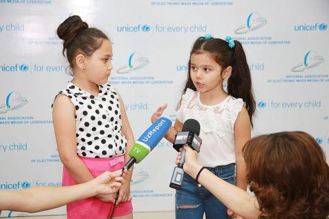 girls being interviewed in front of the banner