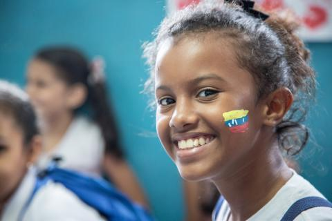 A girls with the Venezuelan flag painted in her face smiles during an art therapy activity