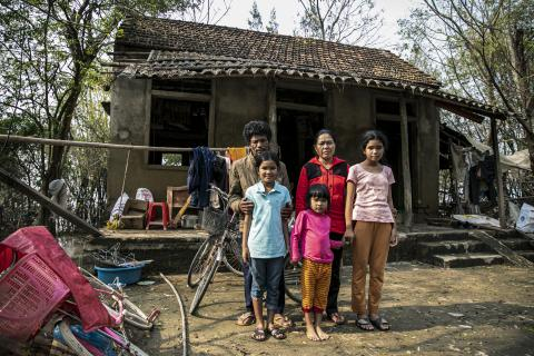 Nguyen Van Hat, 48 years old and his family stand in front of his house built and supported by the local authority some years ago. Mr. Hat's family was reunited a few days after the terrible flood receded.
