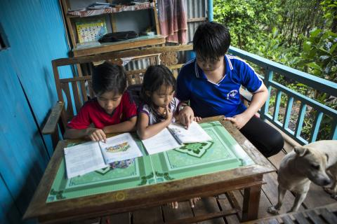 Older brother Tran Anh Bao, pictured right helping his siblings with their homework, played a big role in encouraging his family to install a bathroom and toilet in its home to flush away the threat of disease and stay healthy.