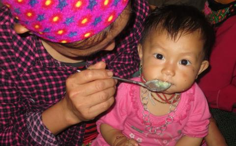 A H'mong infant is fed nutrient-rich porridge, prepared at the child feeding and care club in Lao Cai
