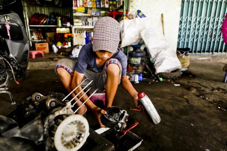 Cậu bé 15 tuổi làm cửa hiệu sửa chữa xe máy ở Vĩnh Thạnh, Đồng Tháp phụ giúp gia đình kiếm thêm thu nhập.