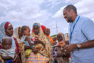 On 28 June 2016 in Nigeria, UNICEF Nutrition Officer Panzomo Usman (right) discusses screening and treatment of severe acute malnutrition (SAM) at the community-based management of acute malnutrition treatment site in Muna-Garage IDP camp, Maiduguri, Borno State.
