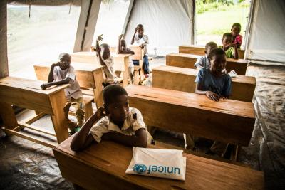Students attend a class in a temporary tent school set up by UNICEF in Mulombela village, Kasaï region, Democratic Republic of the Congo, Thursday 25 January 2018.
