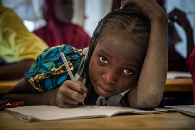 On 17 February, a girl looks up from writing during a class, in a temporary learning space in the Ngagam displacement camp in the Diffa region.