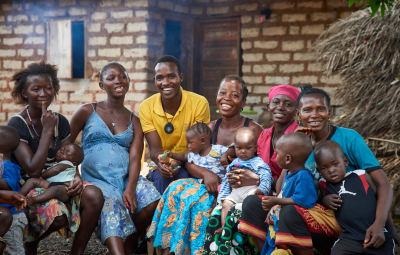 On 30 March, Community Health Worker Osman S. Koroma (centre, in yellow shirt) smiles with women in a mother support group in Kathirie Village in Safroko Limba Chiefdom, Bombali District.
