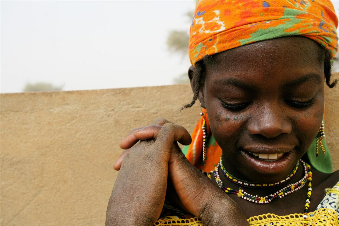 In 2007 in Niger, a girl smiles in the city of Agadez, capital of Agadez Region. She is a member of the Fulani ethnic group.