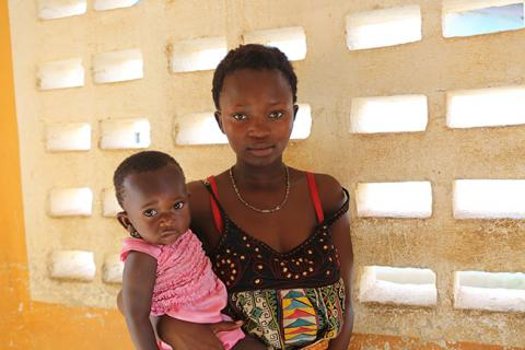 Alice Ngaujah*, 16-years-old stands with her baby outside a girls' centre, in the town of Koidu, eastern Sierra Leone. Last year her parents threw her out of their home when they found out she was pregnant.