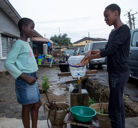 Young girl shows another girl how to wash hands properly