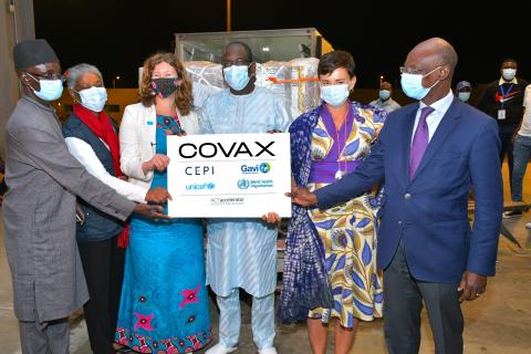 A group of people standing and holding the COVAX sign
