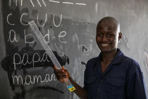 Binef, 18, points at a chalkboard at a protection centre in Côte d'Ivoire.