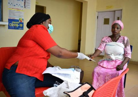 Birth registrar giving out a birth certificate to a mother