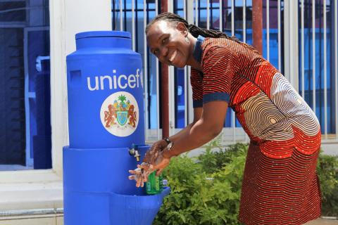 Woman smiles as she washes her hands