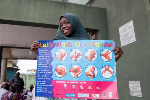 Young girl holds poster which explains how to wash hands properly