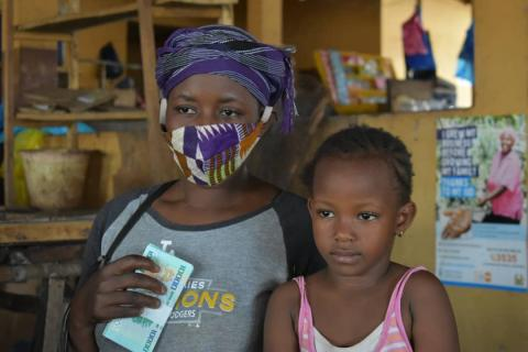 Mother wearing a mask against Covid-19 with her daughter after receiving cash
