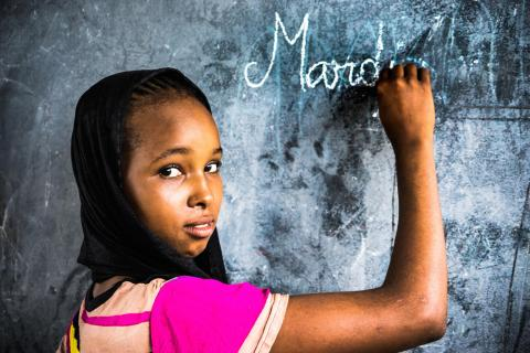 Hawa Oimar, 15, who is in grade CM1, writes on a blackboard in a classroom at the school she attends in Danamadja, southern Chad, Tuesday 13 June 2017.