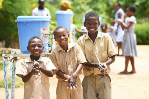 Students smile as they wash their hands