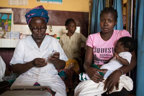 A woman sitting holding her baby who is about to get vaccinated. The nurse preparing the vaccine is sitting next to her