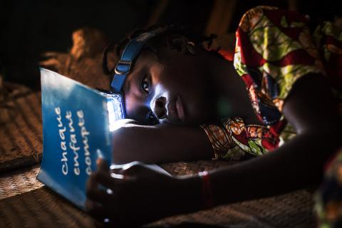 Girl revises her lessons at night using a head lamp