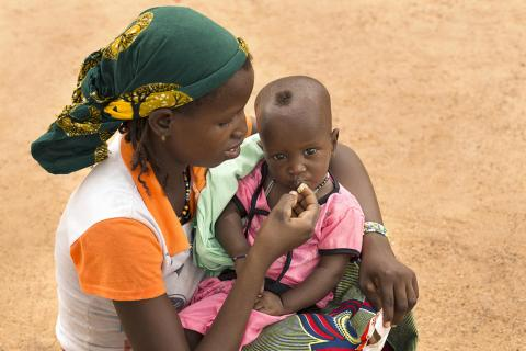 A mother feeding her child Plumpy'nut during an Early Childhood Health Consultation at health facility in Namoungou village, situated around 30 km east of Fada N'gourma in eastern Burkina Faso.