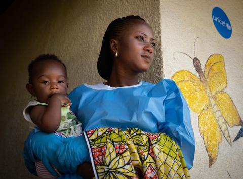 An Ebola survivor, cares for 6 month old Joshua at a UNICEF supported crèche in Beni, in the eastern DRC
