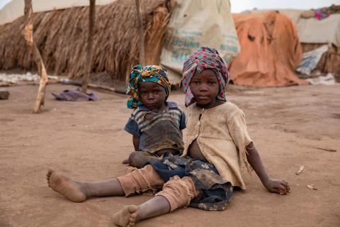 Two boys sitting on the ground outside in the camp for internally displaced persons
