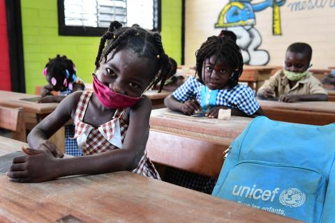 A little girl wearing a mask as she sits on her desk in class, looking at the camera.