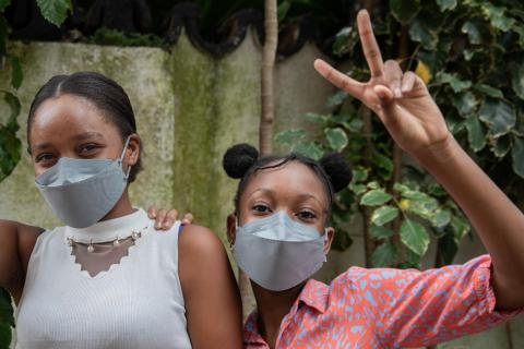 Two adolescent girls facing the camera and wearing masks against COVID-19