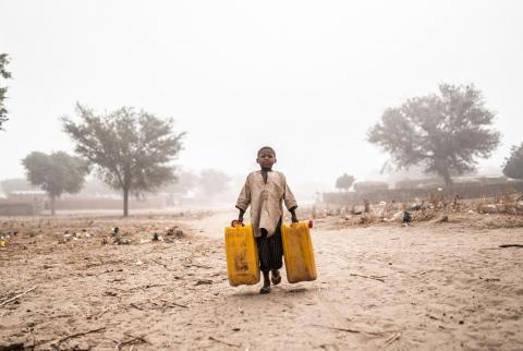 A boy fetch water for his family and the Nigerian refugee family they are hosting at their home in Maradi, Niger.