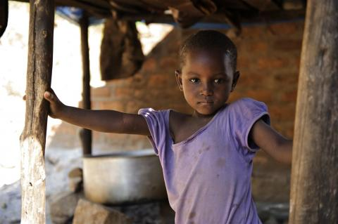 A girl stands outside her house in Rebu Village in Tarime District, Mara Region.