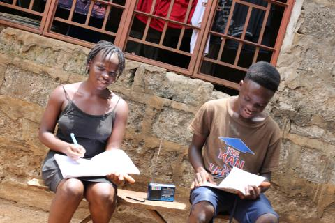 Twins sitting and doing their school work by listening to the radio