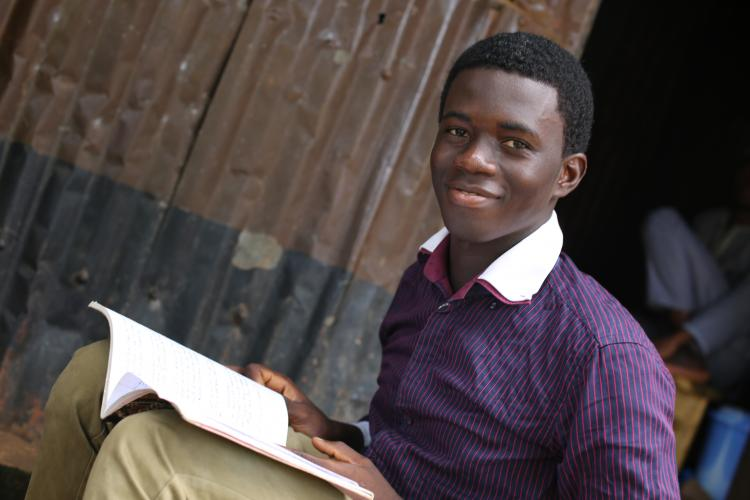 Young man smiles with his notebook open